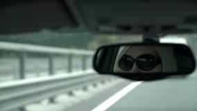 Wijfje met zonnebril in achteruitkijkspiegel stock video