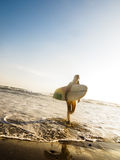 Wijfje surfer met brandingsraad die op strand loopt Stock Afbeeldingen
