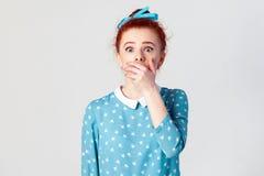 Wijfje in wanhoop en schok Het portret van jong wanhopig roodharigemeisje die in blauwe kleding paniek, behandelde met de hand ha stock foto