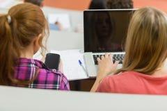 Wijfjes die laptop en cellphone in lezingszaal gebruiken Stock Foto's