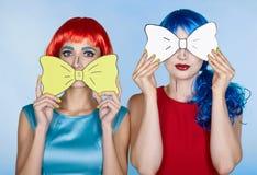 Wijfjes in rode en blauwe pruiken op blauwe achtergrond De meisjes met schreeuwen royalty-vrije stock afbeelding