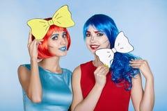 Wijfjes in rode en blauwe pruiken op blauwe achtergrond De meisjes met schreeuwen royalty-vrije stock foto's