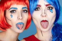 Wijfjes in rode en blauwe pruiken op blauwe achtergrond De meisjes tonen elk stock afbeelding