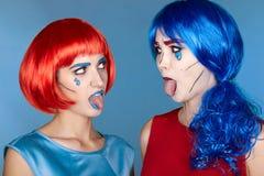 Wijfjes in rode en blauwe pruiken op blauwe achtergrond De meisjes tonen elk royalty-vrije stock afbeeldingen
