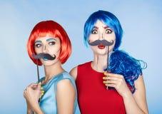 Wijfjes in rode en blauwe pruiken op blauwe achtergrond Meisjes met fal stock afbeelding