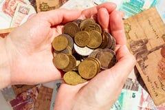 Wijfjeshanden met Euro muntstukken boven de kleurrijke bankbiljettenachtergrond royalty-vrije stock foto