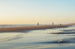 Wijk aan Zee, die Niederlande - 5. Juni 2016: Leute nehmen einen Abendspaziergang entlang dem Strand während des Sonnenuntergangs Stockfotografie