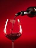 Wijn die op glas rode achtergrond wordt gegoten Stock Foto's