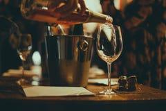Wijn die proeven: op een houten lijst zijn er zilveren emmers voor het koelen van wijnen met flessen champagne, zijn er brochures stock afbeelding