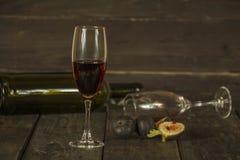 Wijn in een glas een lege fles van fig. op een donkere houten achtergrond Een glas wijn op een houten lijst stock foto's