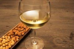 Wijn en amandelokkernoot op houten lijst Royalty-vrije Stock Afbeeldingen