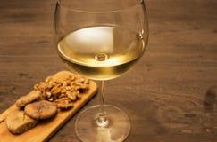 Wijn en okkernootfig. op houten lijst Stock Foto