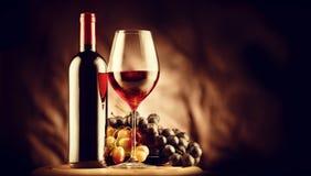 Wijn Fles en glas rode wijn met rijpe druiven stock afbeelding