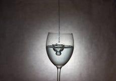 Wijn het Gieten aan Glas Stock Foto