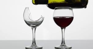 Wijn Rode wijn het gieten in normale en gebroken wijnglazen op de natte oppervlakte stock videobeelden