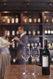 Wijnfles met Twee Glazen, Mensen op de Achtergrond stock fotografie