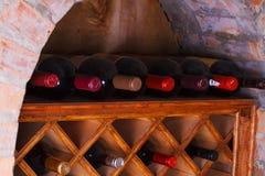 Wijnflessen in de planken worden opgeslagen die Royalty-vrije Stock Afbeeldingen
