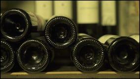 Wijnflessen die in stapel bij kelder dicht omhoog liggen Glasflessen rode en witte die wijn in steenkelder wordt opgeslagen stock video