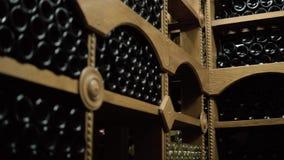 Wijnflessen die in stapel bij kelder liggen Glasflessen rode die wijn in het houten opschorten in steenkelder worden opgeslagen B stock footage