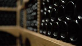 Wijnflessen die in stapel bij kelder liggen Glasflessen rode die wijn in het houten opschorten in steenkelder worden opgeslagen B stock video
