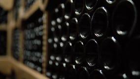 Wijnflessen die in stapel bij kelder liggen Glasflessen rode wijn die in het houten opschorten in steenkelder worden opgeslagen B stock video