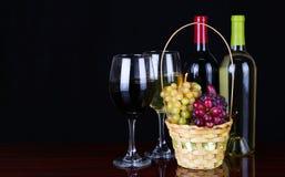 Wijnflessen en Glazen Wijn over zwarte Stock Foto's