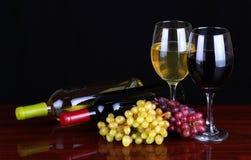Wijnflessen en Glazen Wijn over zwarte Stock Foto