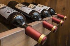 Wijnflessen op rek stock afbeeldingen
