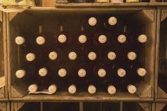 Wijnflessen in wijnkrat, zelf gebrouwen close-up stock fotografie