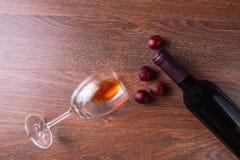 Wijnglas en Wijnfles met Rode Druiven op Houten Achtergrond royalty-vrije stock afbeeldingen