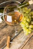 Wijnglas met witte wijn, botlle, kurketrekker en cluster van druiven rond op houten achtergrond Stock Foto