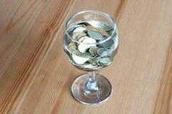 Wijnglas op het geld van lijstmuntstukken besteed aan alcoholclose-up royalty-vrije stock foto's