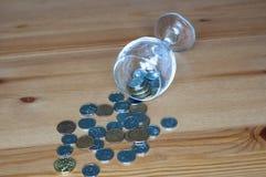 Wijnglas op het geld van lijstmuntstukken besteed aan het alcoholisme van de alcoholclose-up stock foto's