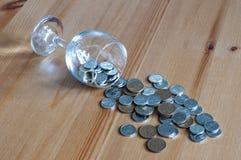 Wijnglas op het geld van lijstmuntstukken besteed aan het alcoholisme van de alcoholclose-up royalty-vrije stock afbeeldingen