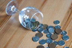 Wijnglas op het geld van lijstmuntstukken besteed aan het alcoholisme van de alcoholclose-up stock fotografie