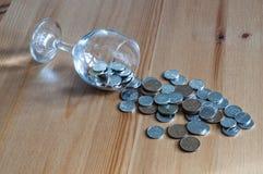 Wijnglas op het geld van lijstmuntstukken besteed aan het alcoholisme van de alcoholclose-up royalty-vrije stock foto