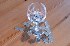 Wijnglas op het geld van lijstmuntstukken besteed aan het alcoholisme van de alcoholclose-up royalty-vrije stock foto's