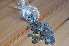 Wijnglas op het geld van lijstmuntstukken besteed aan het alcoholisme van de alcoholclose-up stock afbeeldingen