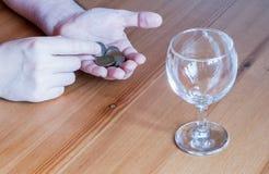 Wijnglas op het geld van lijstmuntstukken besteed aan de handentelling van de alcoholclose-up stock foto