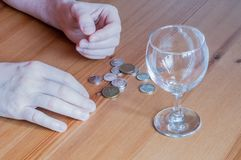 Wijnglas op het geld van lijstmuntstukken besteed aan de handentelling van de alcoholclose-up stock foto's