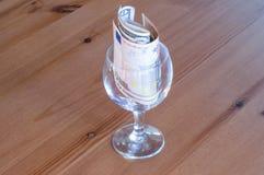 Wijnglas op het papiergeld van lijstmuntstukken besteed aan alcoholclose-up stock foto