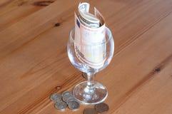Wijnglas op het papiergeld van lijstmuntstukken besteed aan alcoholclose-up stock afbeelding