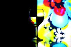 Wijnglas tegen de zwarte en kleurenachtergronden Stock Afbeelding
