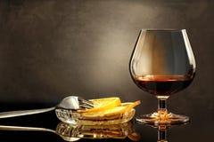 Wijnglas van cognac met citroen en vork op glazige lijst royalty-vrije stock afbeeldingen