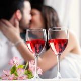 Wijnglazen met paar het kussen op achtergrond stock afbeelding