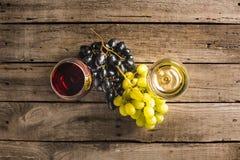 Wijnglazen met wijn en druiven Stock Afbeeldingen