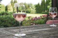 Wijnglazen op lijst bij tuin Stock Fotografie