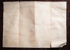 Wijnoogst gebroken leeg gevouwen en verfrommeld document op donkere houten lijst Stock Fotografie