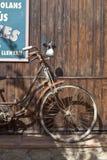 Wijnoogst geroosterde fiets dichtbij een houten muur stock fotografie