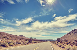 Wijnoogst gestemde woestijnweg tegen zon, reisconcept Stock Afbeelding